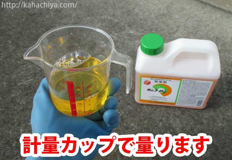 除草剤を計量カップで量ります